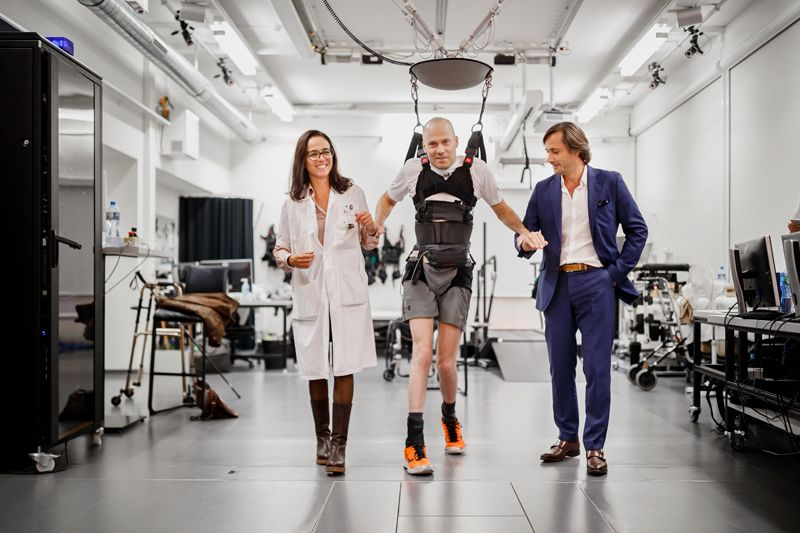 Sebastian Tobler (centre) steps with the aid of researcher Grégoire Courtine (right) and neurosurgeon Jocelyne Bloch.Credit: KEYSTONE/Valentin Flauraud